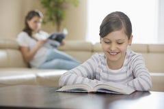与母亲的微笑的女孩阅读书在背景中在家 库存图片