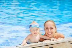 与母亲的男婴游泳滑稽的画象水池的 免版税库存照片