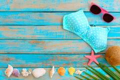 与比基尼泳装、太阳镜、椰子、海星、珊瑚和壳的夏天背景在蓝色木背景 免版税图库摄影