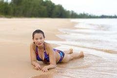 与比基尼泳装的妇女形状俏丽的展示在海滩放松 库存照片
