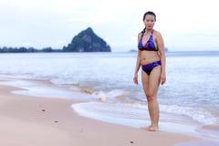 与比基尼泳装的妇女形状美好的展示在海滩放松 库存图片