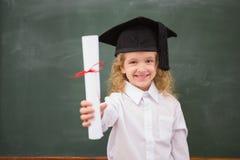 与毕业帽子和拿着她的文凭的学生 免版税库存照片