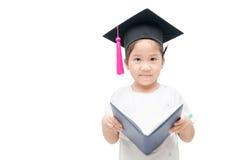 与毕业盖帽的愉快的亚洲学校孩子毕业生阅读书 免版税库存图片