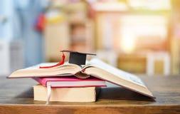 与毕业盖帽的教育概念在木桌上的一本书 免版税图库摄影