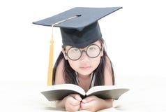 与毕业盖帽isola的亚洲学校孩子毕业生阅读书 免版税库存照片