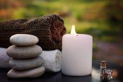 与毛巾、一个灼烧的蜡烛、沭浴油和按摩石头的温泉静物画反对一个绿色庭院的背景 库存图片