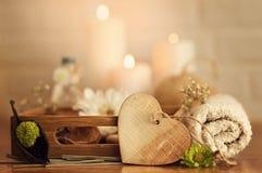 与毛巾、油和木心脏的温泉设置在白色砖背景 免版税库存照片