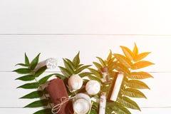 与毛巾和肥皂的温泉集合在与绿色叶子的白色木背景 太阳火光 库存照片