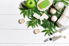 与毛巾和肥皂的温泉集合在与绿色叶子的白色木背景 免版税库存图片