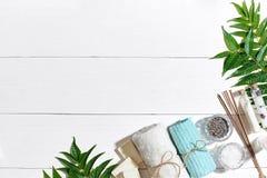 与毛巾和肥皂的温泉集合在与绿色叶子的白色木背景 免版税图库摄影
