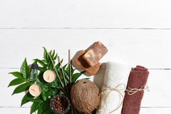 与毛巾和肥皂的温泉集合在与绿色叶子的白色木背景 库存图片