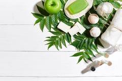 与毛巾和肥皂的温泉集合在与绿色叶子的白色木背景 免版税库存照片