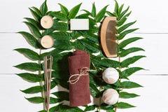 与毛巾和肥皂的温泉集合在与绿色叶子的白色木背景 图库摄影