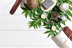 与毛巾和肥皂的温泉集合在与绿色叶子的白色木背景 库存照片