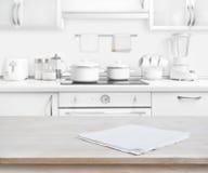 与毛巾的木桌在被弄脏的白色现代厨房背景 免版税库存照片