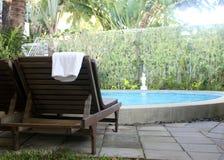与毛巾的海滩睡椅在游泳池附近 图库摄影