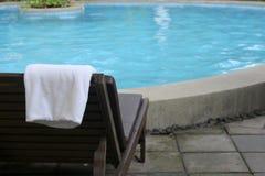 与毛巾的海滩睡椅在游泳池附近 免版税库存图片