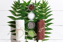 与毛巾的温泉静物画,身体的不同的成份洗刷并且绿化白色木表面上的叶子 免版税库存照片