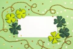 与毛毡叶子和三叶草金黄小珠的空白的白色卡片  库存照片
