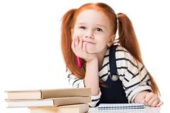 与毡尖笔的沉思微笑的红头发人女小学生图画,当坐在书桌时 免版税库存图片
