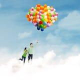 与气球的亚洲夫妇飞行 图库摄影