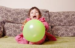 与气球的逗人喜爱的一点女婴戏剧在沙发 免版税库存照片