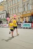 与气球的年轻夫妇奔跑 图库摄影