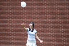 与气球的轻松的亚洲中国女孩戏剧和享受在草坪的业余时间 免版税库存照片