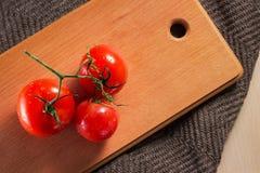 与水和一个绿色分支下落的红色蕃茄在厨房板说谎 图库摄影
