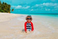 与水和沙子的逗人喜爱的小男孩戏剧在海滩 免版税图库摄影