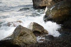 与水和浪花,飞溅的石头 海岸海运 免版税库存照片