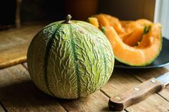 与水多的橙色黏浆状物质的整个和切的成熟有机甜瓜在板材 刀子在木表上的切板 土气的厨房 免版税库存照片