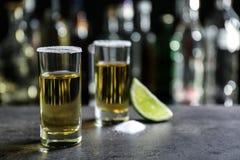 与水多的石灰和盐的金黄龙舌兰酒射击 免版税图库摄影