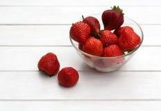 与水多的草莓位置在盘和关闭的静物画在a 免版税库存照片