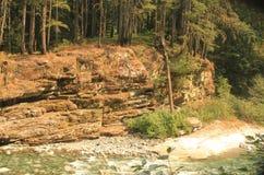 与水平的裂痕的一张小峭壁面孔与跑在它前面的河 图库摄影