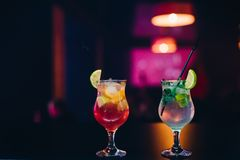与水果鸡尾酒的两块玻璃与石灰、桔子和薄菏和秸杆在党在酒吧 免版税库存图片