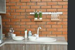 与水槽、洗涤剂和干净的盘的厨台 免版税库存照片