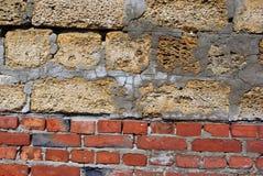与水泥线的克里米亚半岛coquina岩石块在红砖,两不同材料墙壁,关闭纹理 库存图片