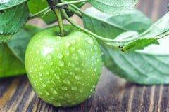 与水滴和叶子在木桌上,宏指令的一个成熟绿色苹果在选择聚焦 免版税库存图片