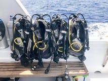 与水管和潜水者夹克的很多黑潜水服在一条快行小船,船,在热带r的巡航划线员的一个立场垂悬 库存图片