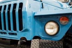 与水箱和车灯的蓝色卡车前面特写镜头 库存照片