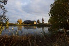 与池塘、房子和教会的秋天风景 库存图片