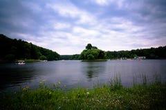 与池塘、脚蹬小船和美丽的多云天空的风景 免版税库存照片