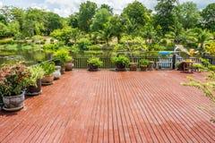 与池塘和庭院的木大阳台 库存照片