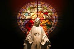 与污迹玻璃窗的圣母玛丽亚雕象 免版税库存照片