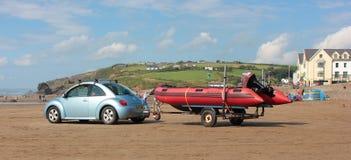 与汽车和充气救生艇拖车2018年8月的海滩场面 库存照片