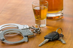 与汽车钥匙和手铐的玻璃 库存照片