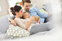 与沙发的看电视的婴孩的年轻家庭 免版税库存照片