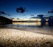 与沙子和云彩的日落与船坞 库存图片