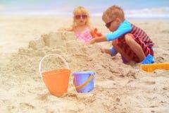 与沙子的孩子戏剧在夏天海滩 库存图片